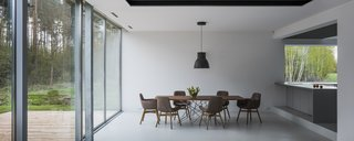 The interior spaces are open, light, and bright.  In the dining room, which sits open to the kitchen, a simple decorative pendant accents a wood dining table.