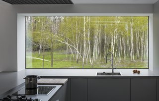 In the kitchen, a large picture window frames views of the surrounding forested land.