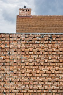 The warm, earthy tones of the brick extend to the roof line, minimizing the visual separation between wall and roof.