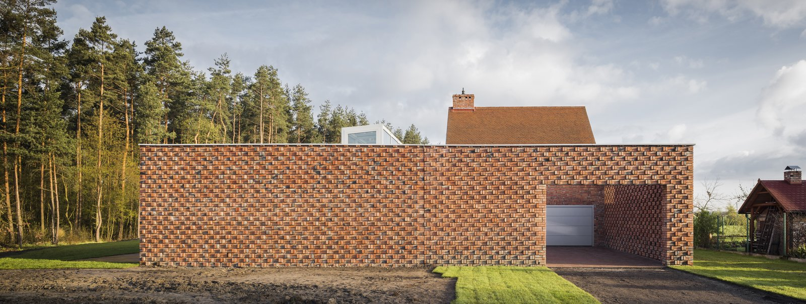 Upon approach, the home appears as a simple horizontal massing, accented by the textural play of crafted brickwork.