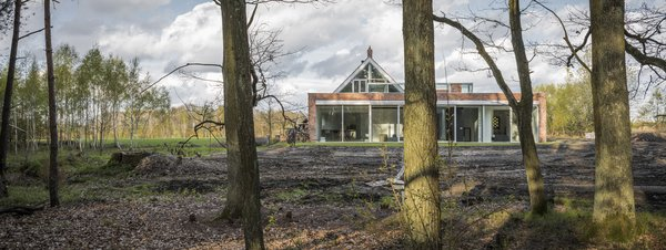 The brick-and-glass Red House sits on the edge of a vast forest glade, nestled in a section specifically allocated for new, single-family development.