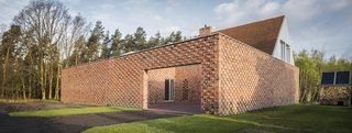 An open brick courtyard defines the entry to the home.