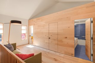 On the second floor, the wood-clad volume conceals two bedrooms and a bathroom.