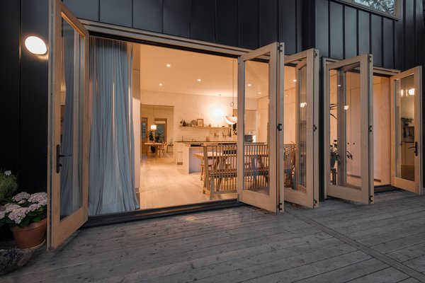 At the rear of the new addition, large folding glass doors open the cooking and dining spaces up to the outside.