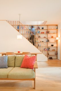 Full-height shelving lines the wood staircase, providing plenty of space for the homeowner's unique collections.