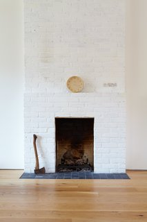 The original brick fireplace stands as a reminder of the home's history.