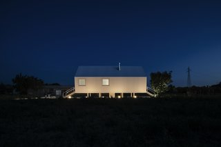 Illuminated from below, the home is a shining light against the dark sky.