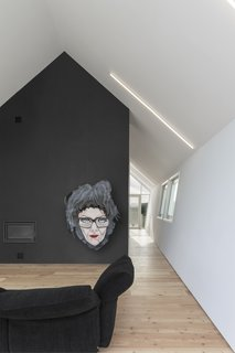 A dark wall decorated with artwork stands as a powerful contrast to the otherwise white interior.
