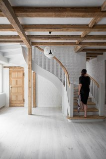 The interior staircase is an elegant contrast with its curved form. Wood stair treads and a wood railing lead to the sleeping and bathing quarters above.