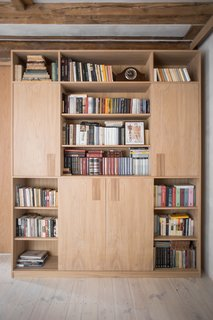 A custom-made shelving unit provides plentiful storage for the family's collection of books.