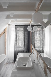 Contemporary lighting and bath fixtures introduce modern touches to the upstairs bath.