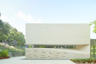 This opaque facade of dry-stacked, brush-hammered Hera limestone faces the neighbors uphill, providing privacy for the occupants.