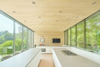 The juxtaposition of open and closed elements continues into the kitchen.  White oak planks wrap the floor, end wall, and ceiling, while floor-to-ceiling glass flanks either side. Low cabinets preserve views to the outside.