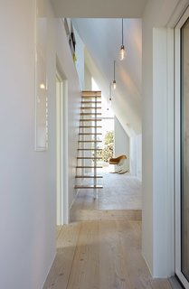 Floating wood stair treads provide an unobstructed view from end to end of the entrance hall, leaving the space open and bright.