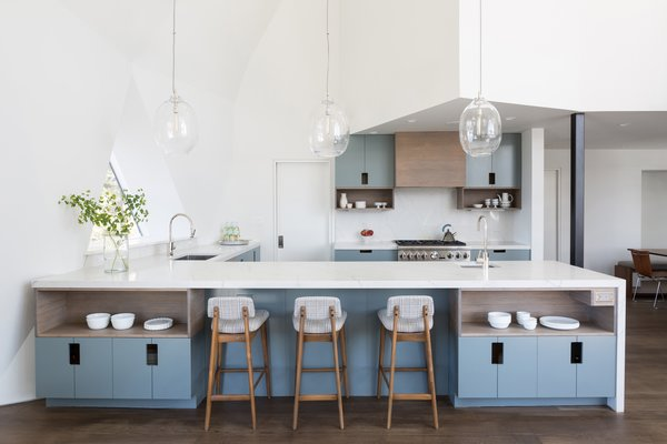 In the kitchen, flat slab cabinetry is finished with gray-blue paint and quartz countertops. A new pantry located behind the kitchen holds the refrigerator, microwave, and pantry shelving.