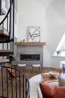 Smooth limestone tiles clad the fireplace, which is topped with an oak mantle. A small seating area with two wood ottomans is arranged adjacent to the fireplace, which opens up to the larger living area.