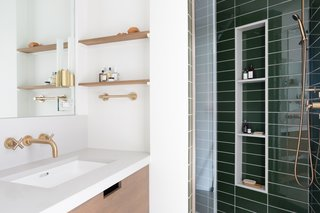 In the master bath, a custom teak vanity is accented by matching floating shelves and satin bronze fixtures. Dark green tiles from Ann Sacks add a deep, rich hue to the master retreat.