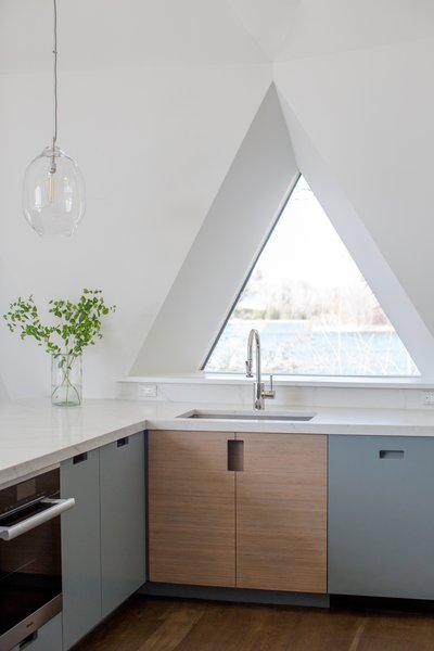 A picture window provides views to the lakefront setting from the kitchen sink. Large glass pendants from Simon Pearce Woodstock hang atop the open work surface.