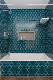 Geometric teal Gotham Swiss Cross tiles by Ann Sacks add playfulness and color to the basement bath.