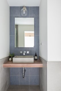 The main floor bathroom was reduced in size to accommodate the new kitchen pantry. The three-quarter bath includes a custom floating walnut slab vanity, dark blue linen-textured tiles, and chrome accents.