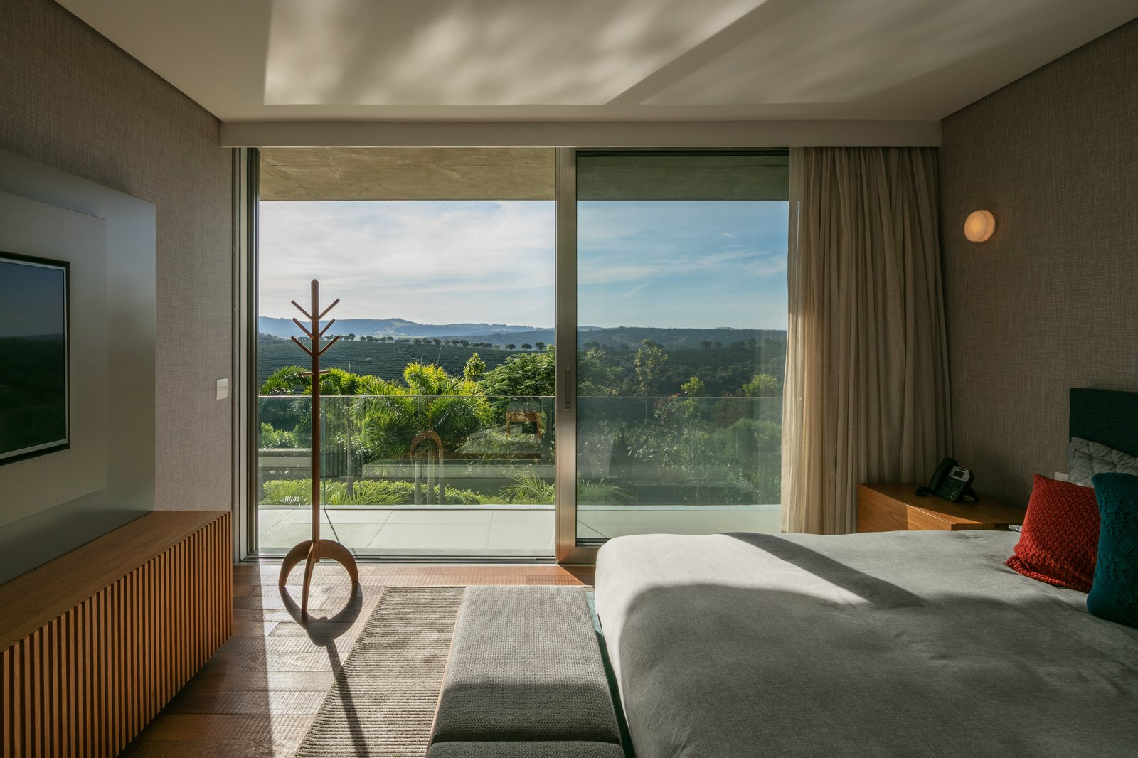 Bedroom, Wall Lighting, Dresser, Bed, and Night Stands Located on the upper floor, stacked above the main living spaces, each sleeping room has its own exquisite views of the surrounding hills.  Photos from This Surprisingly Airy Holiday Home Is Made of Massive Concrete Slabs
