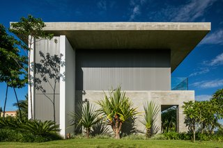 The residence stands out for its simplicity in the use of exposed concrete, metal, and aluminum frames. The simple, long, and narrow volume is accentuated by large eaves that provide shading from the sun's warm rays.