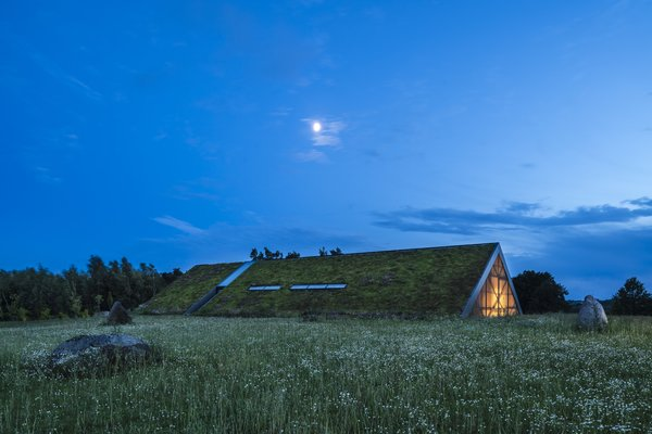 At night, the distinction between site and structure further diminishes as the home's green roof blends into the land.