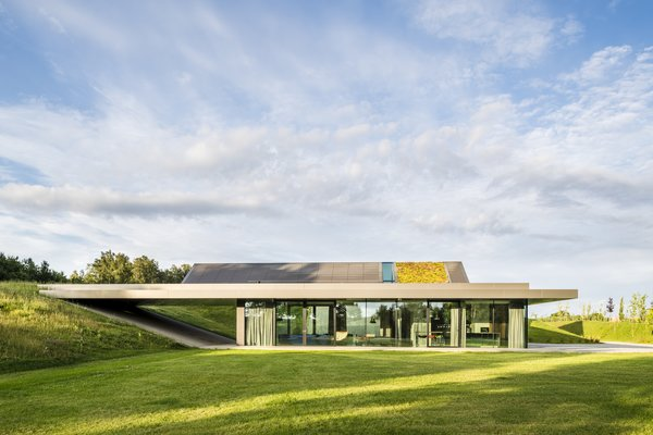 The horizontal concrete assembly appears to hover gently above the landscape, touching only on supporting columns. Floor-to-ceiling glass provides transparency from outside to inside.