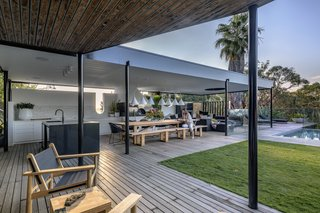 The pavilion surrounds the lawn and infinity pool, providing a covered living space for enjoying the outdoors. Blackbutt hardwood timber decking extends throughout the various programs, providing a feeling of continuity.