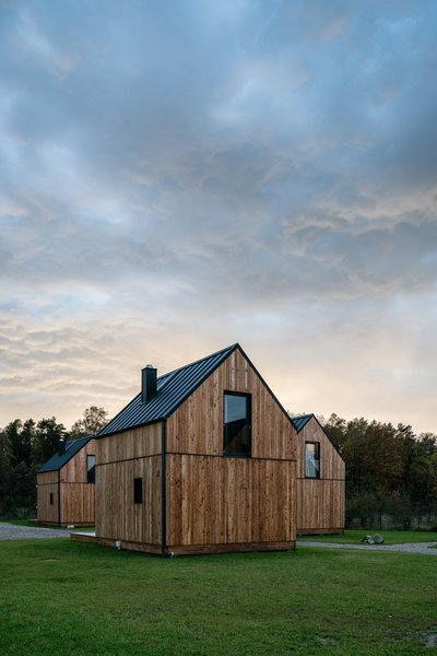 A simple material palette of wood, steel, and glass clads the exterior of each house.