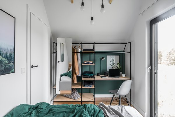 The custom-made furniture is constructed of varnished plywood in combination with black steel frames. Here, a wardrobe and desk are combined as one unit, complete with a full-length mirror.