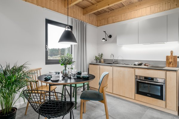 The kitchen may be small and compact, but it provides all the necessities for cooking. Lower birch cabinets combine with white lacquer board uppers, creating a sleek look. A metal-and-leather pendant light by Nordlux hangs above the dining table.
