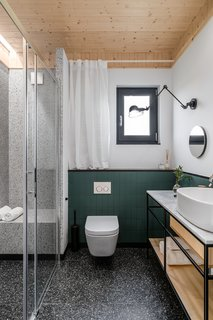 The bathroom is finished with the same green tiles as used in the chimney well. Large-format tiles imitating terrazzo line the bathroom floor and shower walls, including the built-in bench.