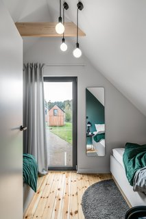 One of the two bedrooms includes two smaller beds. A glass door opens to a small Juliet balcony with a glass rail.