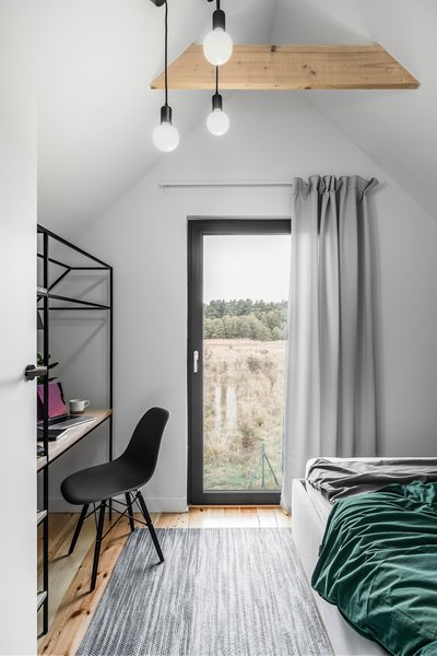 The second of the two bedrooms includes a double bed and desk area. Similarly, the glass door can be opened to further connect the sleeping space to the outdoors.