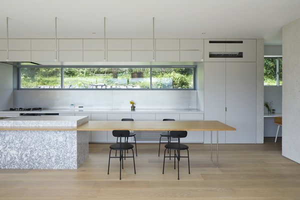 The sculptural marble kitchen island has an extended wood dining surface that forms a breakfast nook. A simple and dramatic pendant light extends the length of the island and is a focal point within the space.