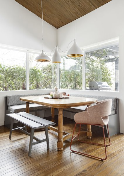 The newly revamped dining area is comfortable and cool with a built-in corner bench, tweed upholstery finishes, and sleek contemporary pendant lights. The homeowners' existing dining room table pairs nicely with the new modern touches, blending old and new.