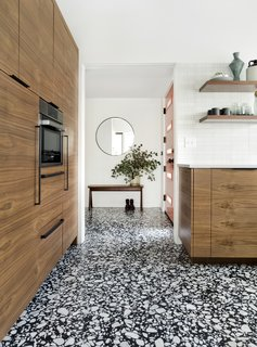 Large format tiles from Ann Sacks resemble traditional mid-century Terrazzo flooring in a bold black and white pattern. By extending the new floor finish into the entryway, the transition between the kitchen and entry is seamless.