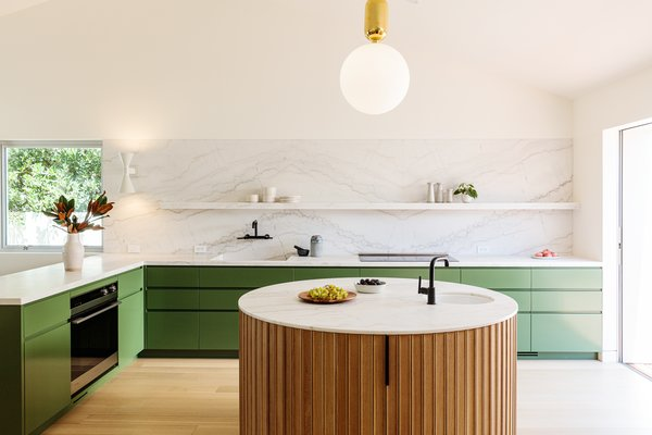 In the kitchen, olive green cabinets pair with Calacatta marble, stylish fixtures, and a circular, wood-clad island.