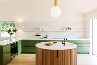 在厨房里,橄榄绿的橱柜搭配着卡拉卡塔大理石、时尚的固定装置和一个圆形的木质岛。