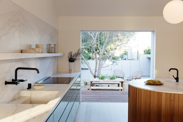 Large sliding glass doors connect the interior living spaces to the outside, providing seamless indoor/outdoor transitions.