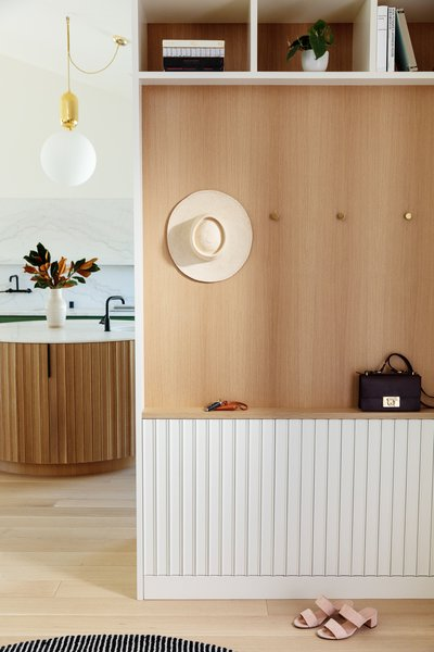 The entry hall is another snapshot of design experimentation with wood built-ins, open cubbies, and simple brass hooks.