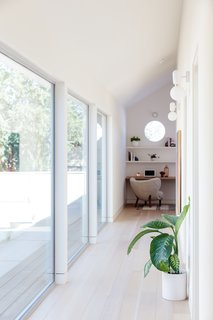 Large windows provide views to the courtyard while drawing in plentiful daylight.  Aballs Wall Sconces from Parachilna march down the hallway to a small office space with built-ins.