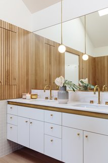 Thin, slatted wood paneling adds warmth to this bathroom.