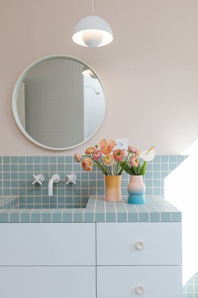 Pastel blue tile and Driklolor paint in the soft, pink Pillow hue add a touch of playfulness to the kid's bathroom. A Flower Pot pendant light from Verner Panton hangs above the round mirror and wall-mount faucet.
