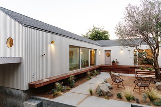 "The original 1,000-square-foot house (where the open living, dining, and kitchen area is mostly located) abuts the new, 1,000-square-foot addition in an ""T"" configuration to make the best use of the site."