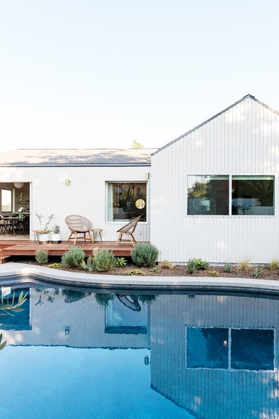 This home's backyard hosts a large swimming pool and deck. Big windows and a sliding door provide indoor/outdoor connections.