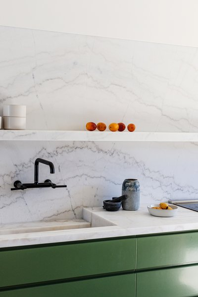 Calacatta marble dramatically extends from the counter and sink to form a backsplash and floating shelf.