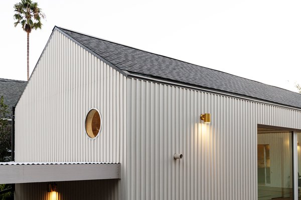 A gabled roof line, metal cladding, and punched window openings keep things simple and clean.