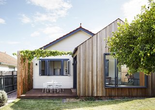 The addition is clad in timber boards of various widths and depths, adding a subtle layer of texture to the simple, gabled form.